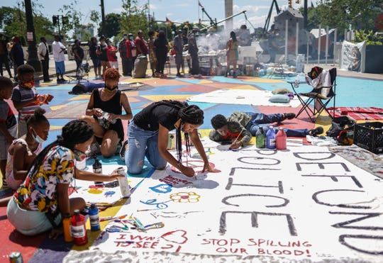 Children work on painting on a banner stating to Defund Police in the 313 Liberation Zone during a separate Juneteenth celebration outside of the Coleman A. Young Municipal Center in downtown Detroit on Friday, June 19, 2020 as others gather for the Juneteenth Freedom Rally put on by the city. The 313 Liberation Zone that was said to  represent the true spirit of Detroit which they believe is a spirit of liberation and abolition also had a a community altar to honor their ancestors that have been killed due to police violence.