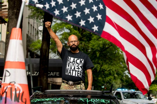 George Floyd's name is written on the windshield as John Coy wears a shirt that reads Black Lives Matter and stands through his sunroof with his fist in the air at 16th Street Northwest renamed Black Lives Matter Plaza near the White House, Friday in Washington.
