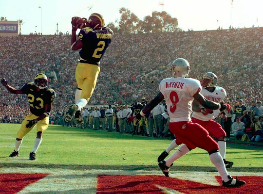 Charles Woodson leaps to make an interception in the end zone during Michigan's Rose Bowl win over Washington State on Jan. 1, 1998.