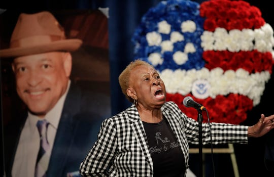 Janie Taylor sings beside a photo of Federal Protective Services Officer Dave Patrick Underwood on Friday in Pinole, Calif. Underwood was fatally shot as he was guarding the Ronald V. Dellums Federal Building in Oakland, Calif., amid protests on May 29.