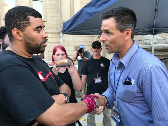 Paul Birdsong of The People of Lansing, a group protesting police brutality, and Ryan Kelley, an organizer of the American Patriot Rally, speak near the Capitol steps on Thursday, June 18, 2020.