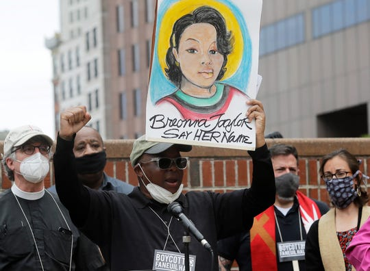 In this June 9, 2020, file photo, Kevin Peterson, center, founder and executive director of the New Democracy Coalition, displays a placard showing Breonna Taylor as he addresses a rally in Boston.