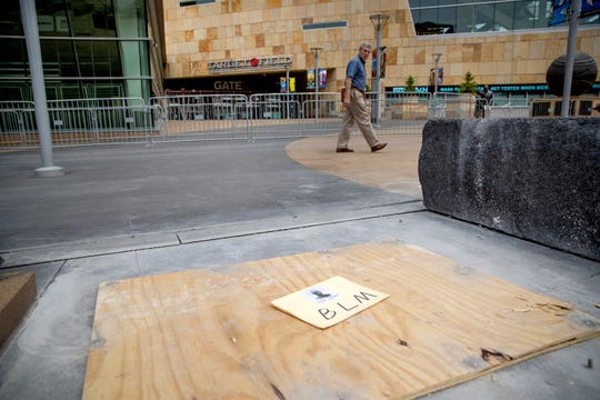 A passerby looks back where a statue of former Minnesota Twins owner Calvin Griffith stood outside Target Field on Friday in Minneapolis, Minn. The baseball club announced Friday that they removed the statue, citing racist remarks Griffith made in 1978.