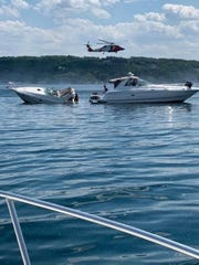 A U.S. Coast Guard rescue swimmer transferred 10 people from a sinking 30-foot vessel to a Good Samaritan vessel in Grand Traverse Bay, Traverse City, June 19, 2020. The vessel sank in about 250-feet of water.