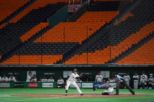 The Yomiuri Giants and Hanshin Tigers play with a backdrop of empty stands during the opening game Friday at the Tokyo Dome.