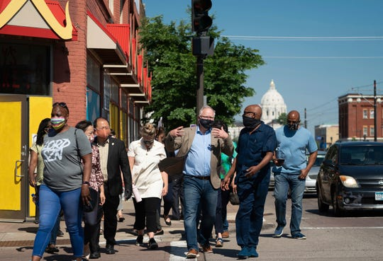 Minnesota Gov. Tim Walz, center, takes a walking tour of some of the artworks commissioned by Springboard for the Arts along University Avenue in St. Paul, Minn., Monday, June 8, 2020.