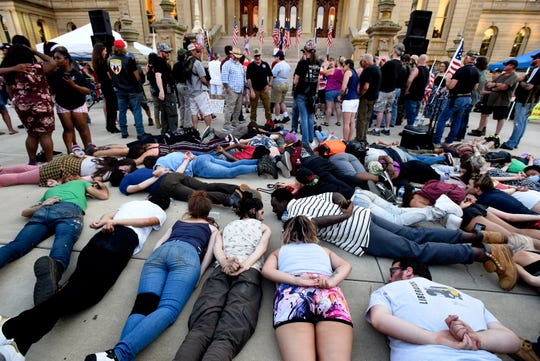 A group of protesters against police violence against African Americans stage a die-in during the  American Patriot Rally for Constitutional Rights at the Capitol Building in Lansing, MI, Thursday, June 18, 2020.