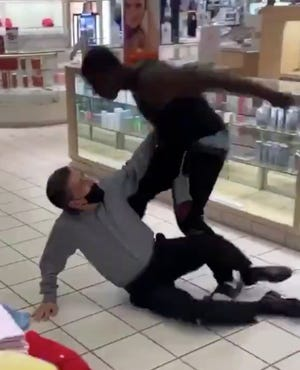 A screenshot from a video posted on Twitter shows one man punching another in the Macy's store at Genesee Valley Center in Flint Township.