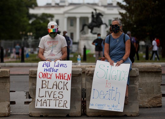 """Rick and Jayna Powell sit on a concrete barricade with signs the read """"All Lives Matter Only When Black Lives Matter"""" and 'Silence is Death We Cannot be Silent Any Longer!"""" Friday in Washington, as the White House is seen behind them."""
