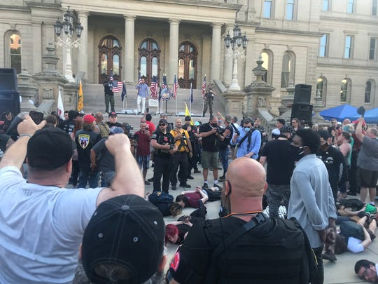 Demonstrators against police brutality lie on the ground in the middle of an event focused on the right to a well-regulated militia outside the Michigan Capitol on  Thursday, June 18, 2020.
