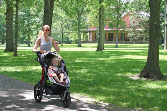 Kelly Fahle of Fremont goes on an afternoon jog at Spiegel Grove, as her daughter Anne enjoys the ride.
