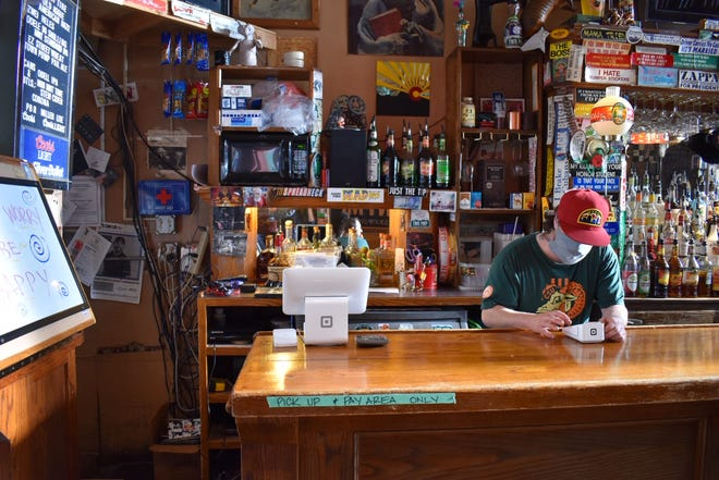 Bartender Rob Fitz rings in an order at Town Pump, the oldest bar in Fort Collins, Wednesday, June 17. The College Avenue mainstay was almost forced to close its doors due to coronavirus-related restrictions on bars and restaurants earlier this year.