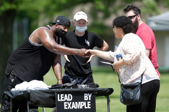 Daniel Gilbert of Kimberly talks with customers while selling his Lead by Example apparel on Friday at a Juneteenth celebration in Perkins Park in Green Bay.