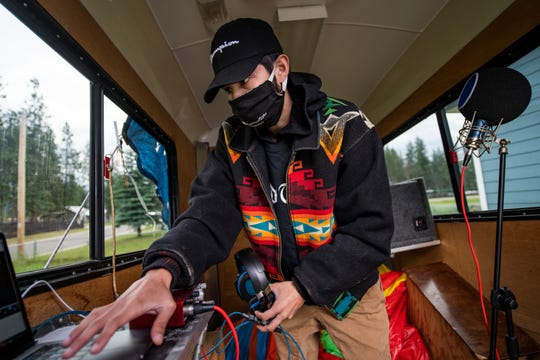 In this photo taken June 16, 2020, Artie Mendoza III, also known as KiidTruth, works on a new track in his home studio in Pablo, Montana. Mendoza created a viral TIk Tok dance and song to promote hand washing, mask wearing and social distancing among the youth on the Flathead Indian Reservation. (AP Photo/Tommy Martino)