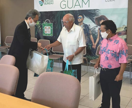 Toshiaki Kobayashi, consulate general of Japan to Guam, accepts a welcome gift from former Gov. Carl T.C. Gutierrez, GVB president and CEO, and GVB Board Chairman P. Sonny Ada at the GVB office in Tumon.