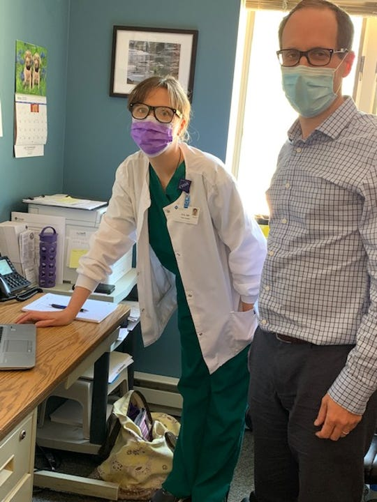 Nurse Erin Shepherd assists Dr. Douglas MacQueen, an infectious disease doctor at Cayuga Medical Center, during the COVID-19 pandemic.