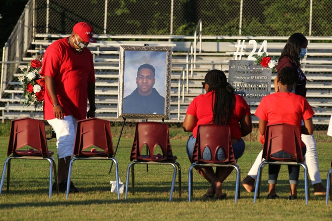 Family members take their seats as they pass a portrait of Jakobe Cooper before a candlelight vigil for Cooper on Thursday, June 18, 2020 in Shannon, Miss.  Cooper died during football practice on Tuesday.