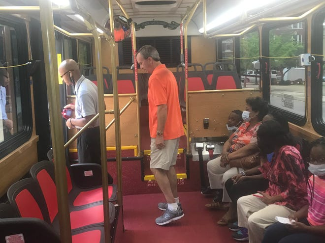 Visitors tour the inside of the trolley-like bus that was unveiled Thursday.