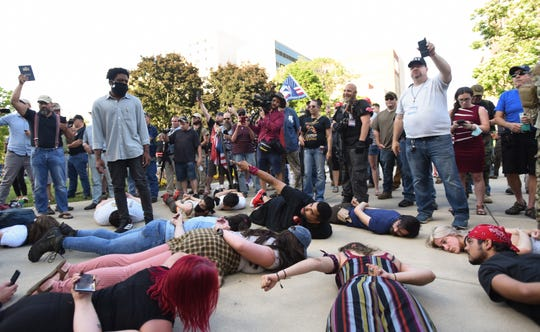 """The """"American Patriot Rally""""was in full swingwhen a group of people who have staged nightly demonstrations in the Lansing area strolled into the middle of the crowd and lay face-down on the pavement.  [MATTHEW DAE SMITH/USA Today Network]"""