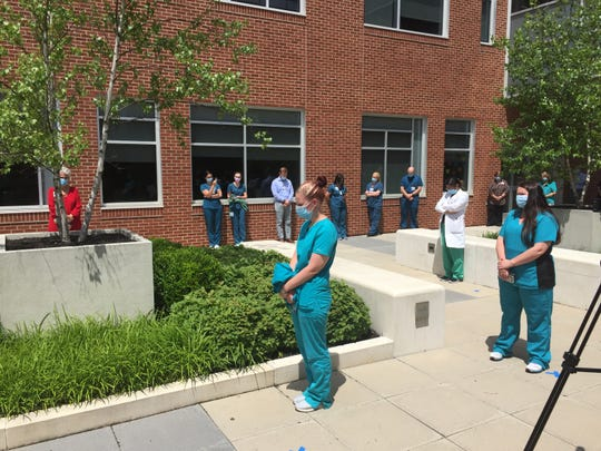 People observe a moment of silence in honor of George Floyd at a Friday ceremony at OhioHealth Mansfield Hospital to recognize Juneteenth.