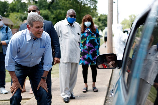 Tennessee Gov. Bill Lee talks to an unidentified woman at the COVID-19 testing site at Mississippi Boulevard Christian Church in Memphis, Tenn., on Friday, June 19, 2020.   Lee was in Memphis to check in on two of the free testing sites being held over the weekend.
