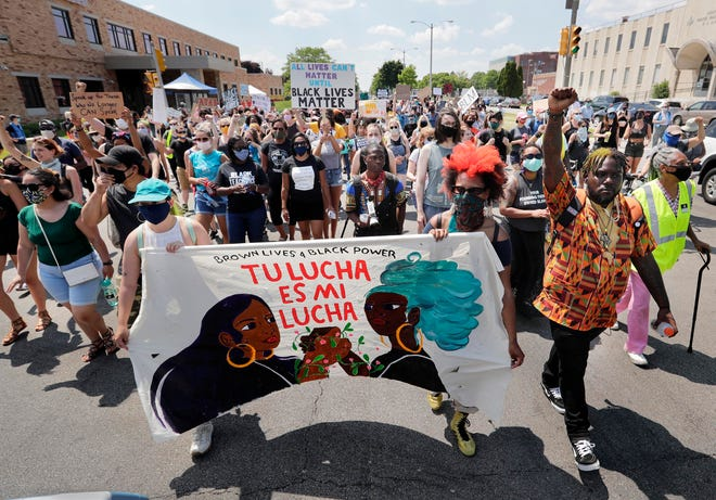 Several hundred protesters march past St. Francis of Assisi Catholic Church in observance of the Emancipation Proclamation, and to celebrate the mothers of the freedom movement,  on Friday, June 19, 2020, in Milwaukee. They started the march at the Sojourner Family Peace Center.