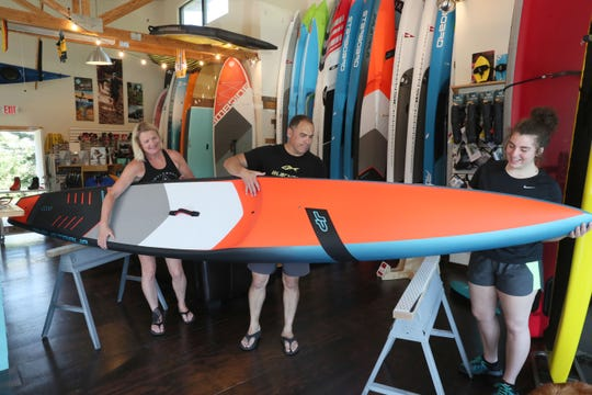 June 18, 2020 Photographs from Paddleboard and Nordic Specialists in Oconomowoc.  Paddleboard and Nordic Specialists owners Cris Rosario center, and his wife Susanna Rosario, left, assisted by their daughter Sophia Rosario, check over a new 14 foot race paddle board, all carbon fiber made by JP Australia, before putting it on display.