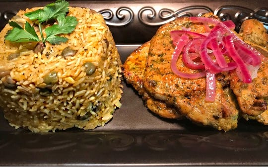 Empanada Sonata serves a variety of Cuban dishes, including this colorful rice and pork chops topped with pickled onions.