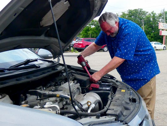 Kent Curry, owner of Batteries Unlimited, changes a car battery for a client in the parking lot of the Heath business.