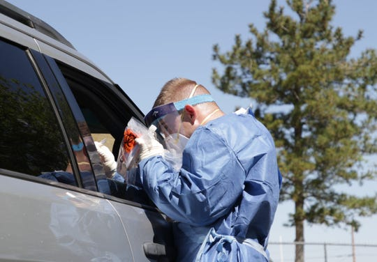 A health care professional collects a sample during the free testing site for COVID-19 on May 5, 2020 at Shiprock High School in Shiprock.