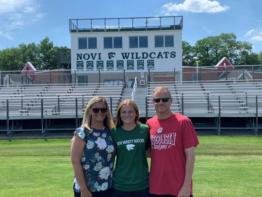 Novi's Avery Fenchel stands with her parents at Novi's soccer field.