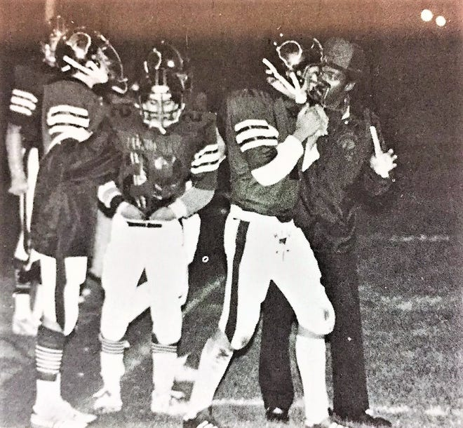The author, Ed Wright, senior quarterback at Lansing Hill in 1979, gets the next play from Billy Hawkins, the man firmly believed to be  the first Black high school head football coach in Lansing's history.