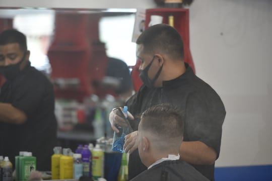 Pompy's in downtown Chambersburg reopened shop on Friday, with barbers donning masks.