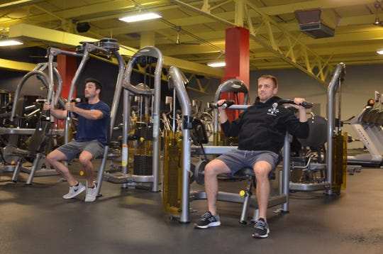 """Alex Crilley and Dylan Bryan, employees at WBO Health and Fitness utilize the equipment. Bryan said they were busy on their first morning open. """"People were happy to be back,"""" he said. """"They kept their distance like they were supposed to and cleaned the equipment like they were supposed to."""""""