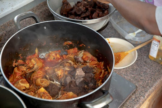 Ola Elkaknah adds fried beef shank to her vegetable stew, she is cooking for a catering customer in Salem, Oregon, on Wednesday, June 17, 2020. She cooks local cuisine for the small African community in Salem.