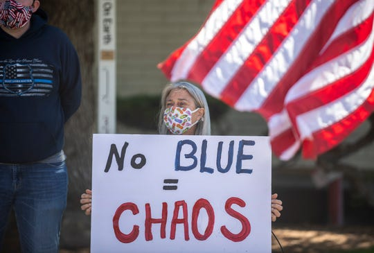 "Dawn Jones, holds a sign that reads ""No blue = chaos"" during the MC Blue Rally held outside of city hall in Salinas, Calif., on Thursday, June 18, 2020."