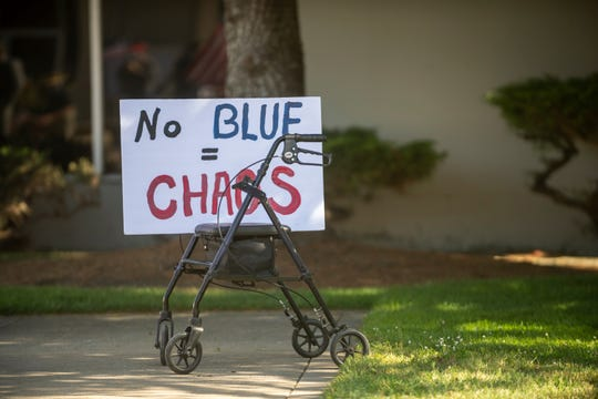 "A sign that reads ""No blue = chaos"" sits on top of a walker during a pro law-enforcement protest in Salinas, Calif., on Thursday, June 18, 2020."