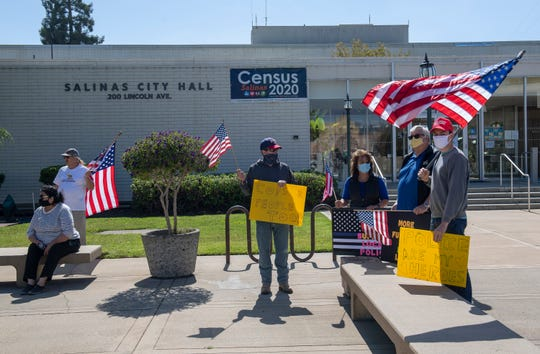 Pro law-enforcement protesters hold different sized American flags to show their support for the local police officers outside of city hall in Salinas, Calif., on Thursday, June 18, 2020.