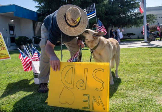 Dennis Boesider, holds a few signs as his dog Reyna gives him a kiss  before the start of a pro law-enforcement protest outside of city hall in Salinas, Calif., on Thursday, June 18, 2020.