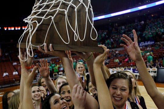 The Wall High School girls basketball team hoists the 2014 state championship trophy after their 48-44 upset win over Brock.