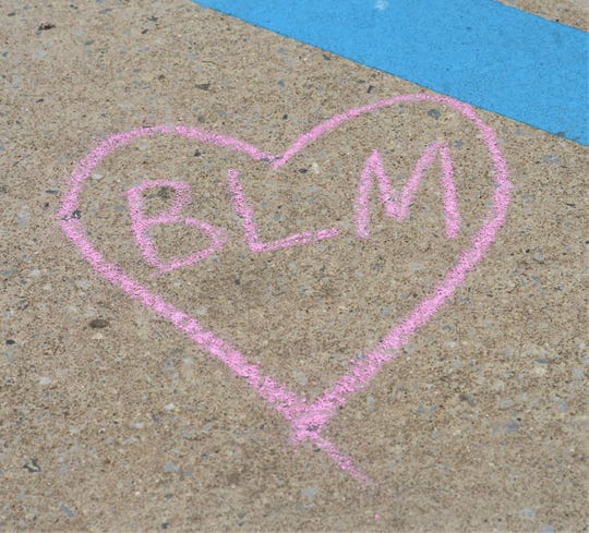 A heart that pays homage to the Black Lives Matter movement is written on the sidewalk of the newly renamed Black Lives Matter Blvd. on Friday, June 19, 2020.