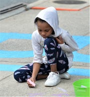 A child writes a message on the sidewalk of the newly renamed Black Lives Matter Blvd. on Friday, June 19, 2020.