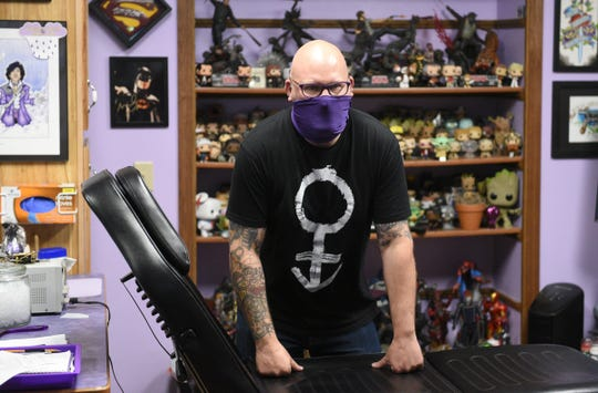 Erik Cagle, owner of Purple Pain Tattoo Studio, leans on the chair in his studio Thursday, June 18, 2020, in St. Cloud.