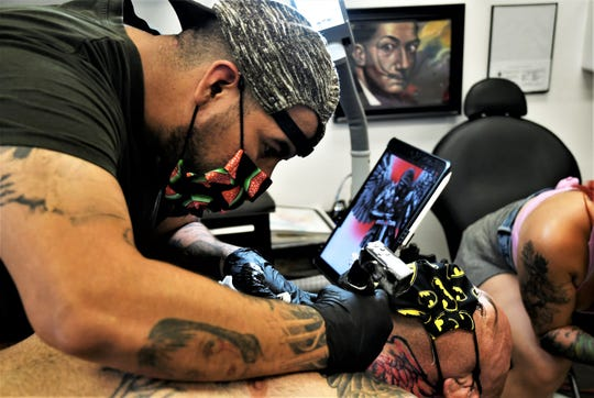 Joseph Cabello, owner of Tulare's Body Art Gallery, tattoos Doug Marshall on Friday, June 19, 2020.