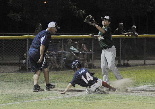 Visalia National's Payton Allen (14) slides safely back onto third base before Porterville's Johnny Herrera (20) during a Little League championship game in Exeter in 2013. Allen's father, Jody, is coaching third base.