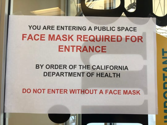 A sign tells Visalia Toyota customers that a mask is required to enter.
