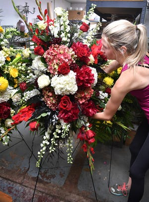 Jenny Hines, owner of Jameson's Flowers, puts the final touches on one of several large flower arrangement for Noel Johnson's funeral Friday afternoon.