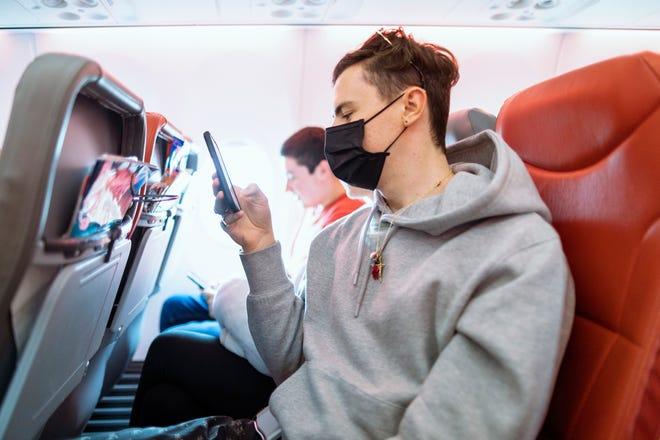 Pasajeros con mascarilla a bordo de un avión.