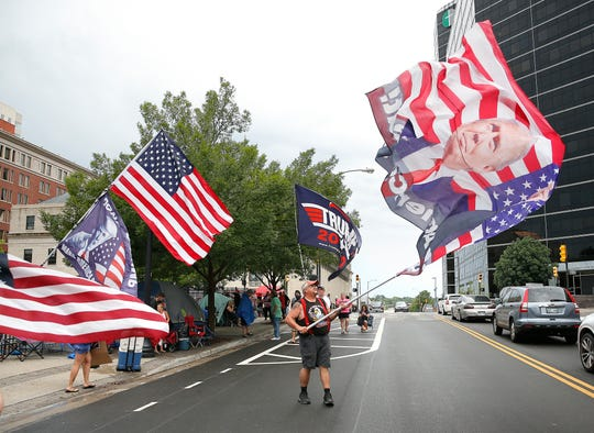 Randal Thom waves a Trump flag in downtown Tulsa ahead of President Donald Trump's Saturday campaign rally, Friday, June 19, 2020.