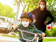 Child riding bike with mask while mom watches